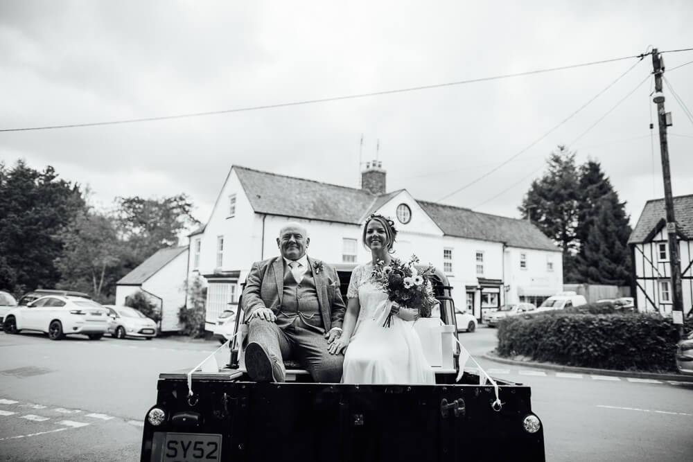 bride and father on the back of a land rover
