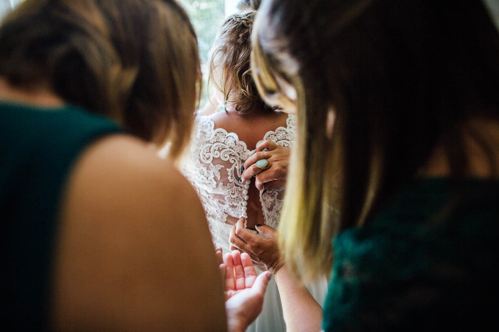 Brides dress being buttoned up